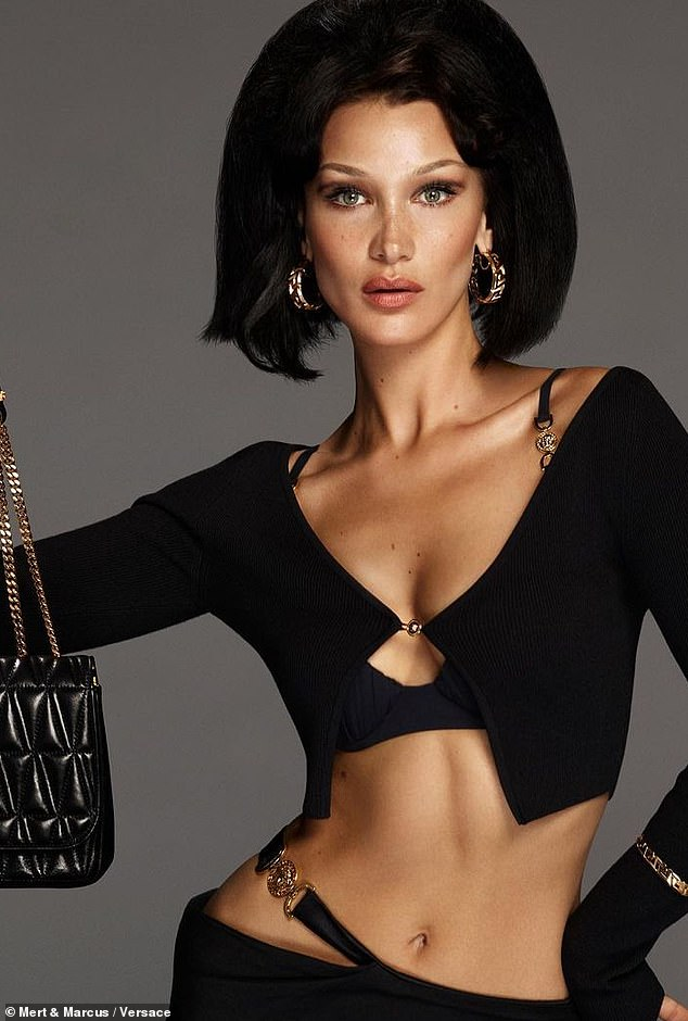 Abs time: And the mermaid held up a Versace handbag in black with bronze hardware. Her hair was worn in a 1960s bouffant style as she had it on large earrings and a bangle