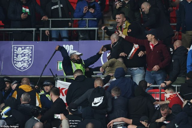 An officer uses his baton to hit out and force away Hungary fans, who fought back against the police inside the stadium