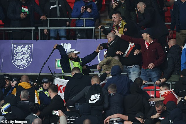 A police officer strikes a Hungary fan with his baton during ugly scenes at Wembley Stadium