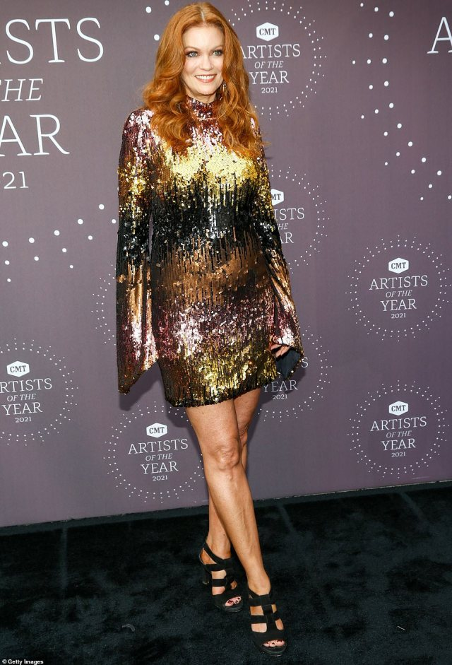 There she is:Alecia Davis let her fiery red hair fall free over a shimmering chrome dress that featured gold, bronze, black and pink, complementing the outfit with black heels