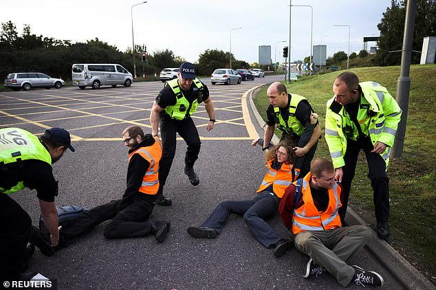Police officers remove Insulate Britain activists as they block junction 31 of the M25 yesterday