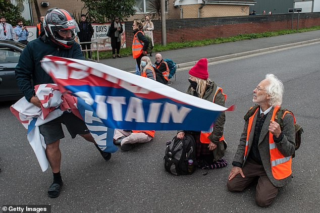Angry motorists snatch banners from protestors as activists from Insulate Britain block parts of Thurrock yesterday morning