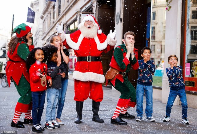 Elves and children pose for a photograph outside Hamleys toy store in London with Father Christmas this morning