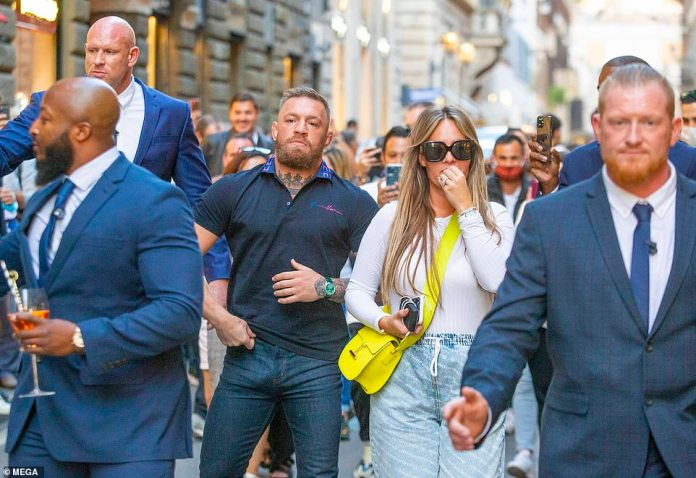 Keeping him safe: He was surrounded by the security guards as he walked down the street with Dee