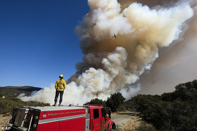 A firefighter watches on his fire engine as smoke rises from a wildfire in Goleta, California onWednesday