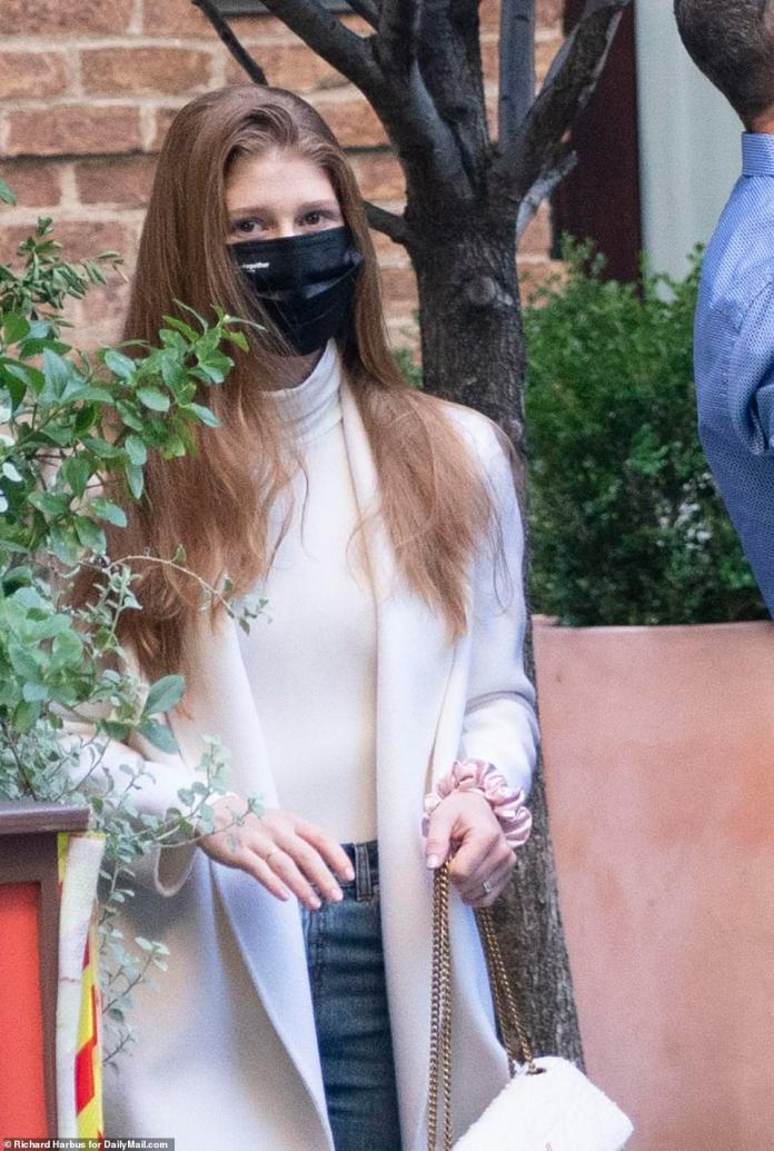 The 25-year-old, who is due to tie the knot in North Salem, New York on Saturday, looked elegant in a cream-colored duster coat, white turtleneck, blue jeans and chain-strap purse