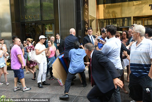 Trump's former director of security and longtime bodyguard Keith Schiller (right) reaches for protester Efrain Galicia (center in a blue shirt) on September 3, 2015