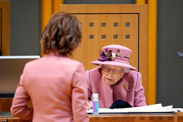 Queen Elizabeth II signs a document inside the Siambr (Chamber) during the ceremonial opening of the Sixth Senedd in Cardiff