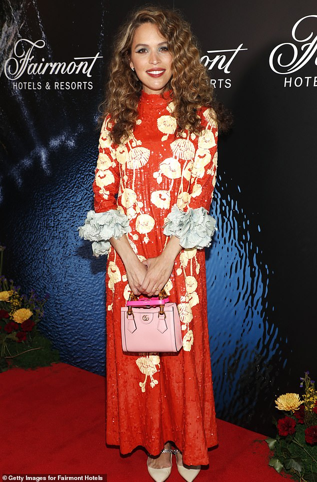 On the town:Cleo, who is now the Fairmont brand's 'poet-in-residence,' cut a summery figure in a bright red and gold floral frock with flowery blue cuffs