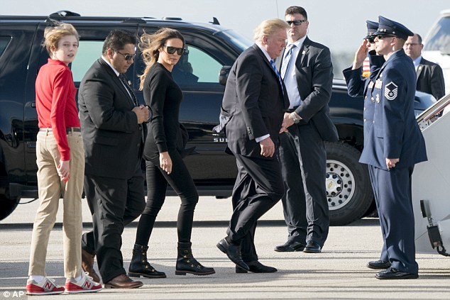 Barron Trump (left) wearing New Balance sneakers that match his red, long-sleeved shirt turns to look at the press as first lady Melania Trump (center) and President Trump (right) board Air Force One Monday afternoon
