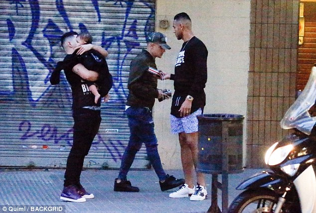Coutinho (centre) watched on with his friends after visiting theSagrada Familia temple