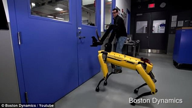 The man first stops the robot with a hockey stick, pushing a new arm attachment away from the door. When that doesn't work, he closes the door against the robot to prevent it from opening it, before pulling it backwards