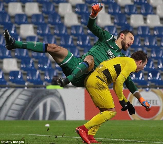 Atalanta goalkeeperEtrit Berisha falls awkwardly after clashing with Dortmund's Gotze