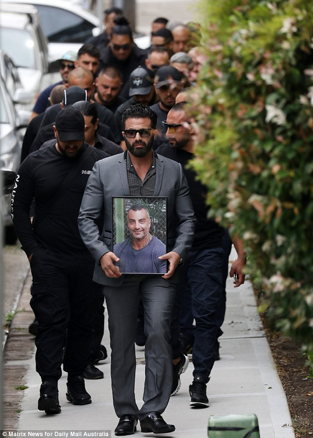 Mourners at Mick Hawi's funeral on Thursday are led by a man carrying a picture of the bikie
