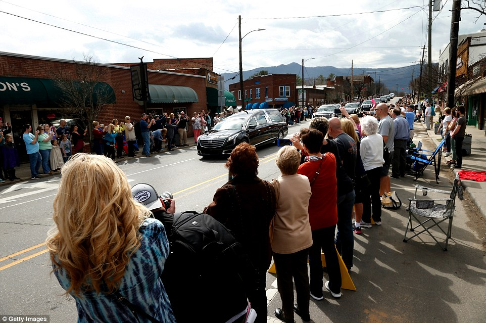 Residents pay their respects as a motorcade carrying the Rev. Billy Graham's body to Charlotte's Graham Library rolls through a downtown shopping district on February 24, 2018 in Black Mountain