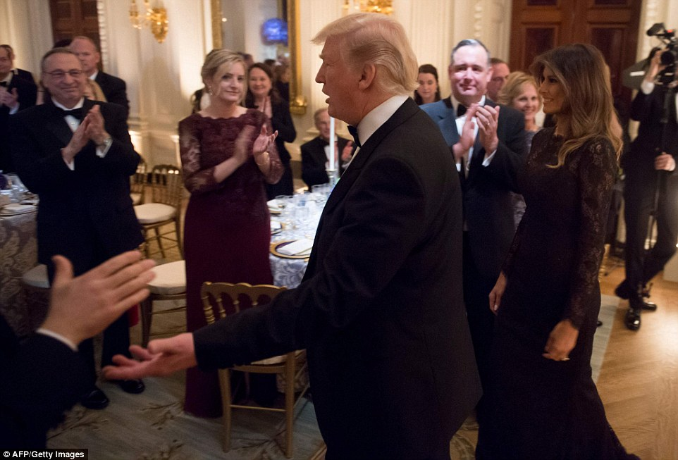 President Donald trump and First Lady Melania Trump are pictured entering the East Room of the White House to a standing ovation