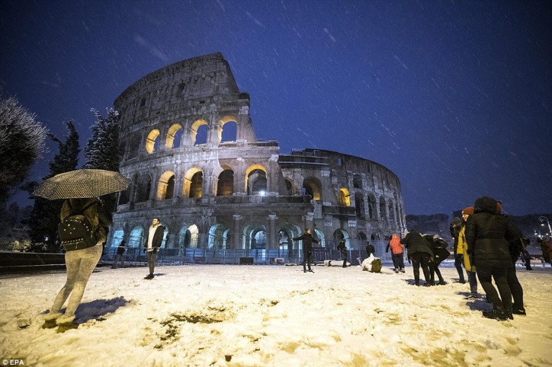 Tourists stand in front of the Colosseum in Rome after the famous landmark was covered with snow after a storm on Monday