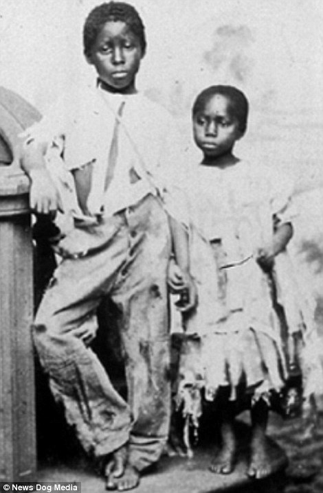 A brother and sister, former slaves, holding hands and wearing ripped and torn clothing. They were owned by Thomas White of Mathews County, Virginia, until Captain Riley, 6th USOI, turned them over to the Society of Friends to educate at the Orphan's Shelter in Philadelphia. The photograph is entitled 'As we found them'