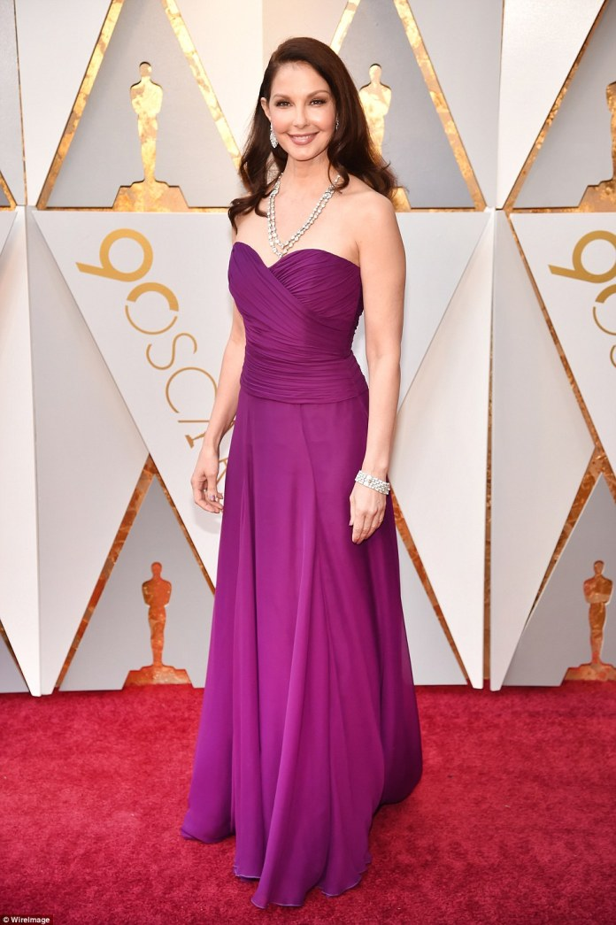 Glowing:Ashley Judd brought bold tones to the carpet; The actress and activist chose a ruched purple gown with a strapless neckline by Badgley Mischka; the beauty added even more glamour with her chunky diamond necklace and earrings