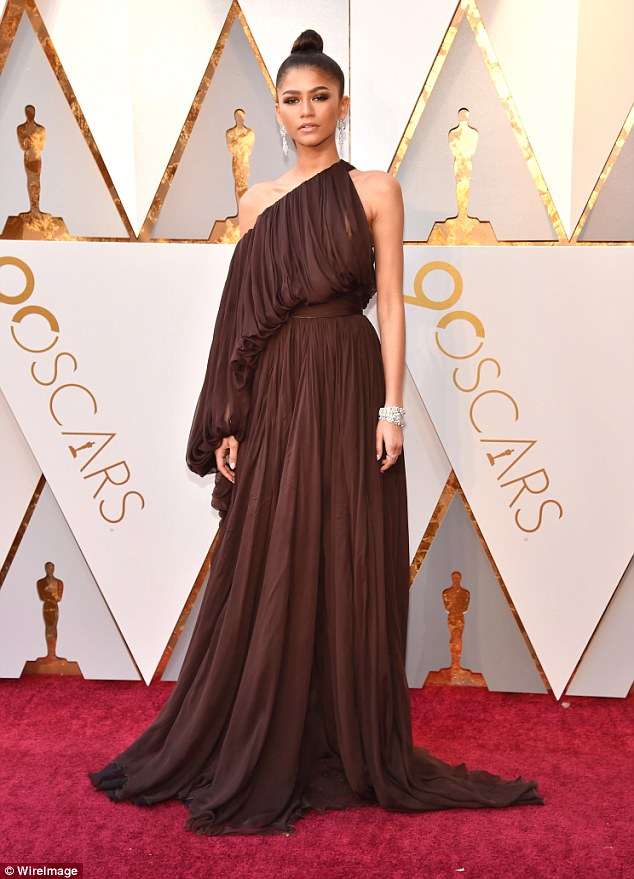 Eye-catching: Zendaya put on a stylish show at the Oscars on Sunday in Hollywood, arriving on the red carpet at the Dolby Theatre wearing a dark chocolate chiffon gown