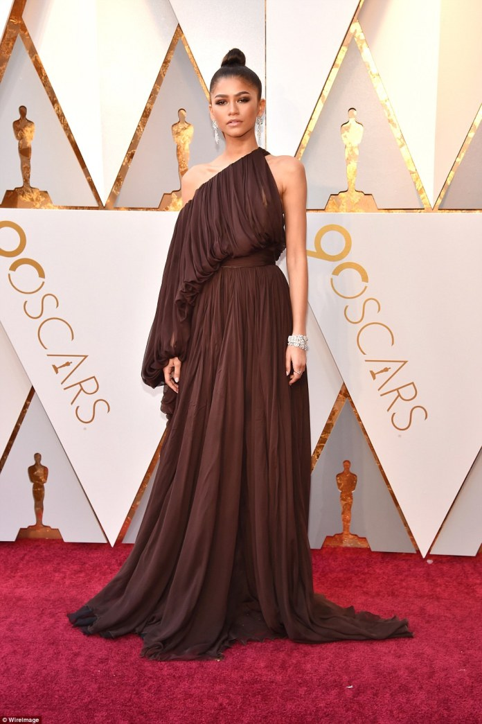 A goddess: Zendaya chose a chocolate hued one-shoulder gown with a pleated texture; she wore her locks in a top knot; she wore a Giambattista Valli Spring 2018 Haute Couture dress
