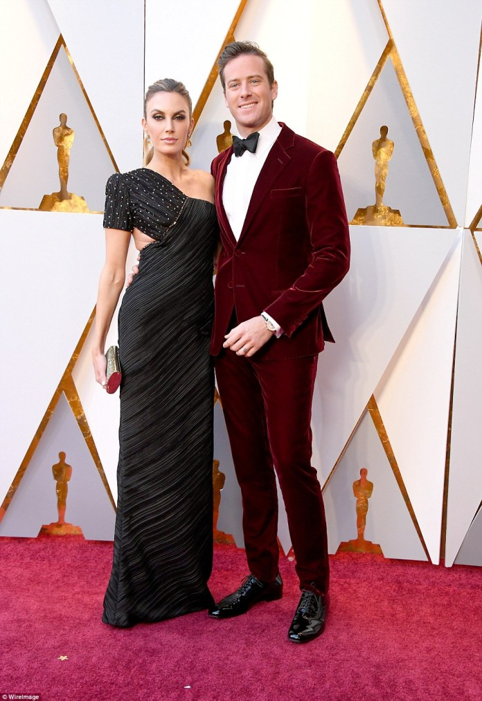 Looking good: Armie Hammer posed with his gorgeous wife Elizabeth Chambers, who donned a black and gold sequined look by Armani Prive from their Spring 2017 collection; Armie donned a Giorgio Armani suit