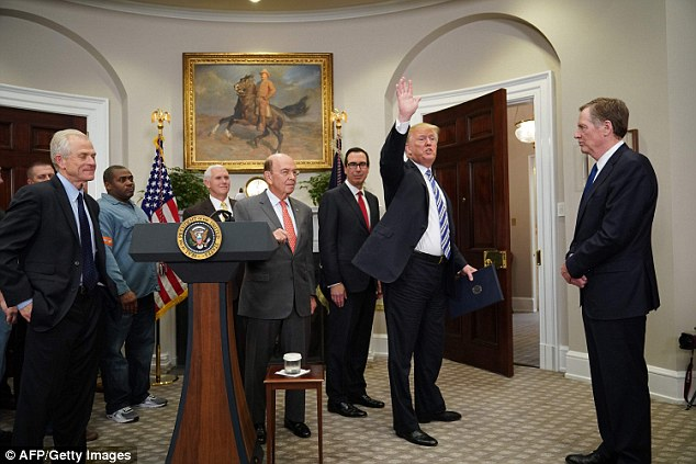 Trump invited the workers to take photos of the Oval Office, forgetting to actually sign the proclamation until Treasury Secretary Steve Mnuchin (3rd from right) reminded him to