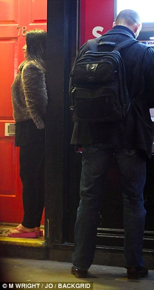 She can be seen leaning against a doorway next to the cash machine Fiennes is using