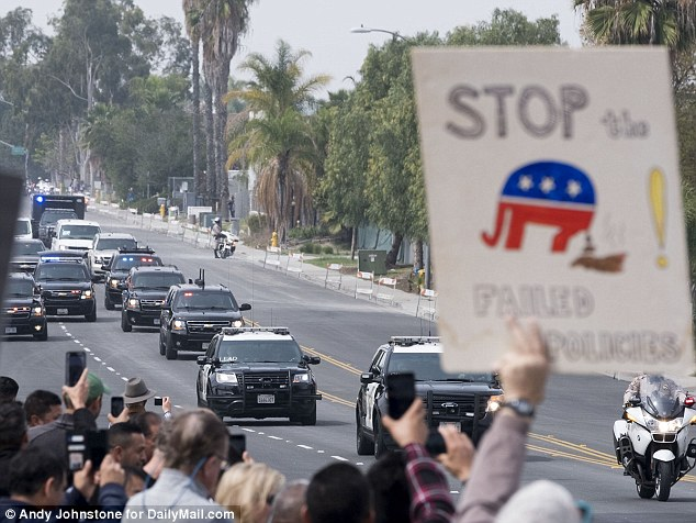 A protester's sign is seen as President Trump arrives at the U.S.-Mexico border in San Diego, California on Tuesday