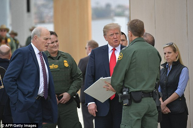 President Trump (center) takes a look at border wall designs in San Diego, California flanked by his Chief of Staff John Kelly (left) and Department of Homeland Security SecretaryKirstjen Nielsen (right)