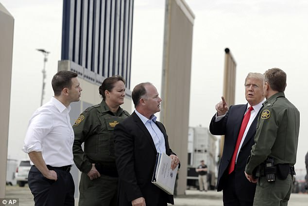 A number of border wall prototypes are seen looming behind President Trump  (right) as