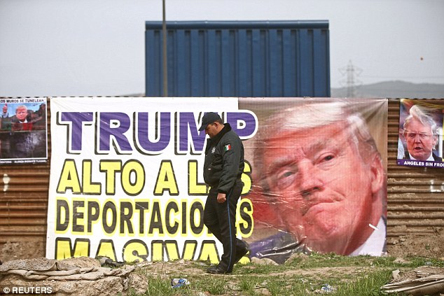 A sign on the Mexican side of the border reads 'Trump, stop mass deportations.' It hangs on the current border fence that the president wants to replace with a taller, more fortified wall