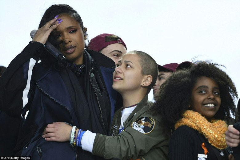 Hudson is a victim of gun violence too. Her mother, brother and nephew were all murdered in 2008. They were shot to death. She is pictured hugging Stoneman Douglas student Emma Gonzalez as 11-year-old Naomi Wadler, one of the event speakers, looks out towards the crowd