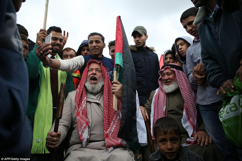 Modern protest: A Palestinian youth takes a selfie while an older man chants slogans as he holds a Palestinian flag during protests east of Jabalia in the Gaza strip