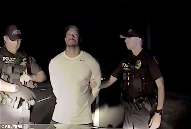Tiger Woods is seen handcuffed and searched by police officers in this still image from police dashcam video in Jupiter, Florida, U.S. on May 29, 2017