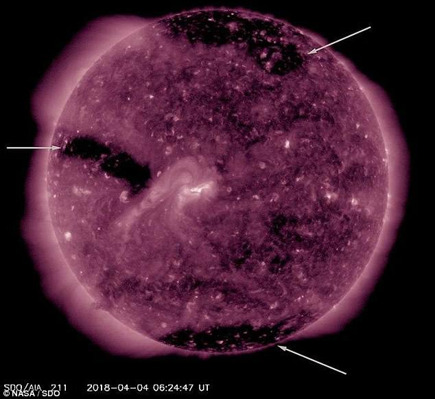 Strong solar winds emanating from three massive 'holes' on the surface of the sun have begun to bombard Earth, scientists say. Fast moving solar winds are created where the star¿s magnetic field opens up into space, captured as vast black regions in this satellite imagery