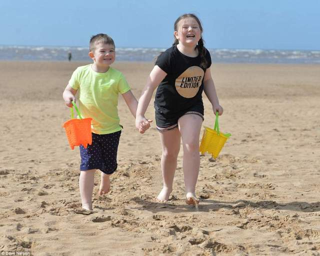 Carter Martin, 5, and his sister Zara, 9, from Birmingham, play on St Anne's Beach in Blackpool in their shorts and t shirts in the sunshine