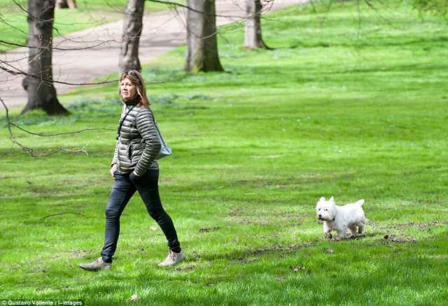A woman and her Scottish Terrier enjoy the afternoon at Green Park in London as Britain prepares to bask in the hottest April day for ten years