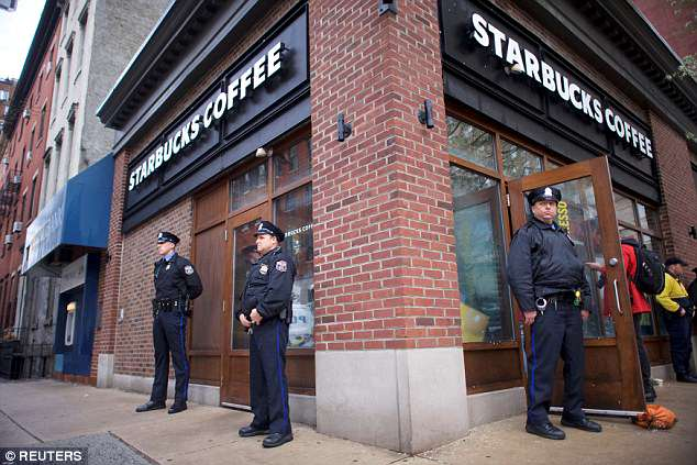 Police officers monitor activity outside as protesters demonstrate inside the Starbucks store where the two men were arrested last Thursday