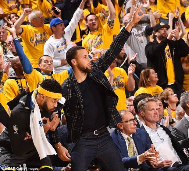 Stephen Curry watched from the sidelines as he nurses a sprained left knee injury