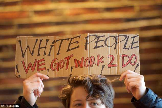 A protester holds up a sign which reads 'White people, we got work 2 do' on Monday