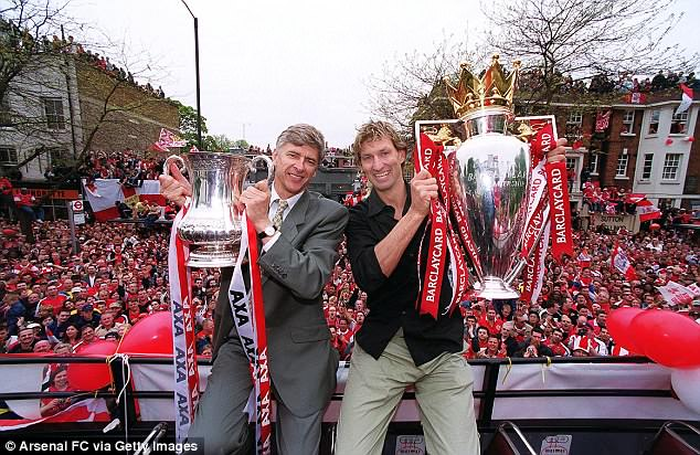 Wenger, alongside Arsenal legend Tony Adams here, also won a record-breaking seven FA Cup