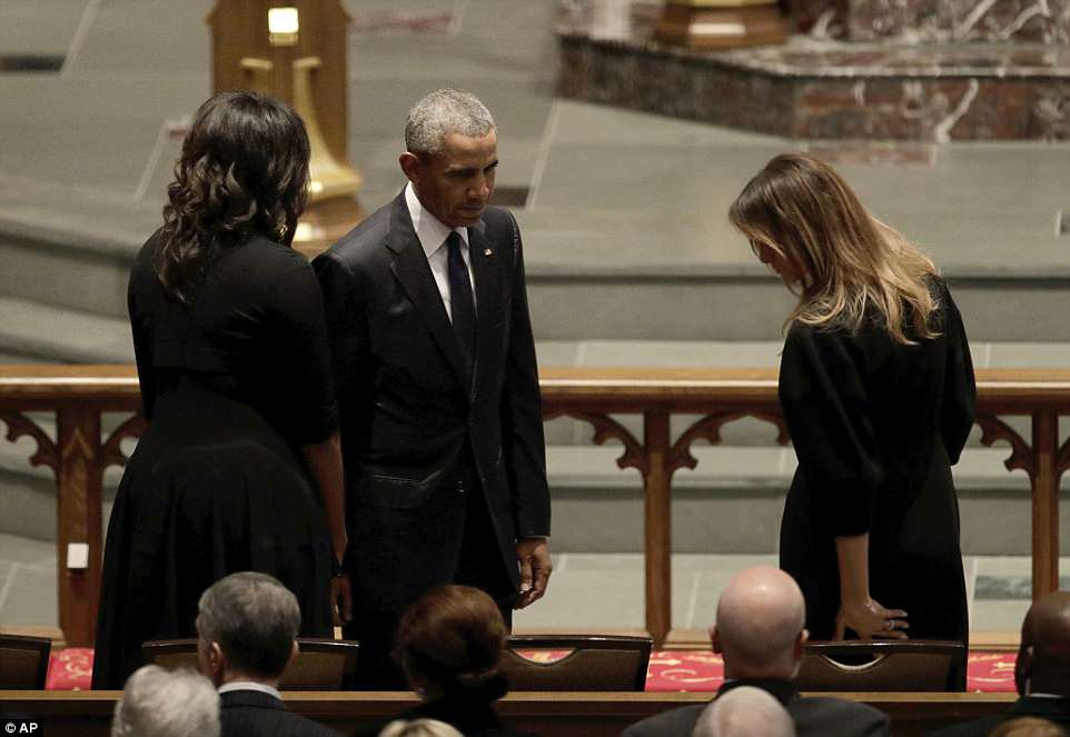 Gentleman: Barack Obama waits to take his seat next to Melania with wife Michelle by his side