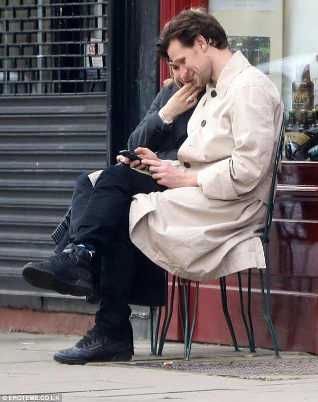 Sweet: During their romantic outing, the pair giggled at their phones as they sat outside a shop