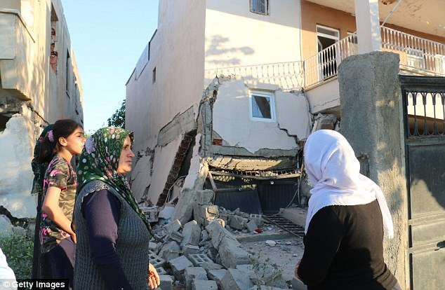 Damage: Women gather near a partly collapsed building in Samsat district of Turkey's Adiyaman province on Tuesday morning