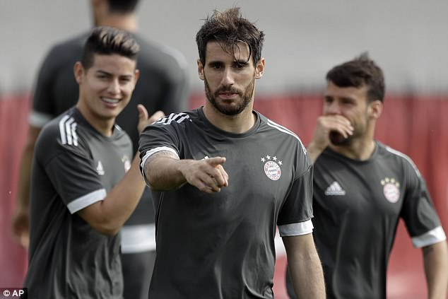 Javi Martinez (C) gestures during training  with James Rodriguez (L) and Juan Bernat (R)