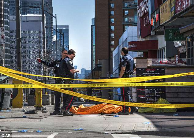 Police officers stand by a covered body in Toronto after the deadly van attack Monday