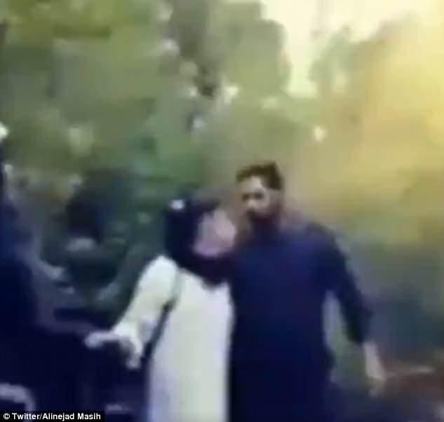 Se ve a un hombre de pie junto a una mujer que camina en público con el pelo descubierto en Irán