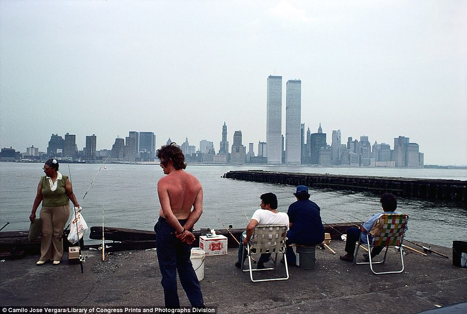 View of Lower Manhattan from Jersey City, New Jersey, in 1977. This photograph shows the World Trade Center (1973-2001) tower over the Manhattan skyline as people fishing from a pier in New Jersey