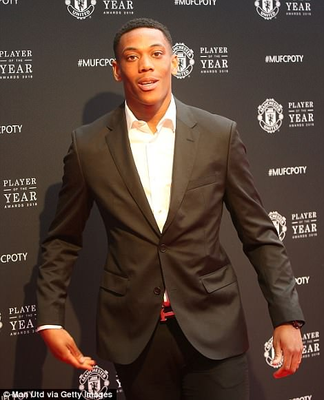 Anthony Martial poses as he wears a suit jacket but no tie